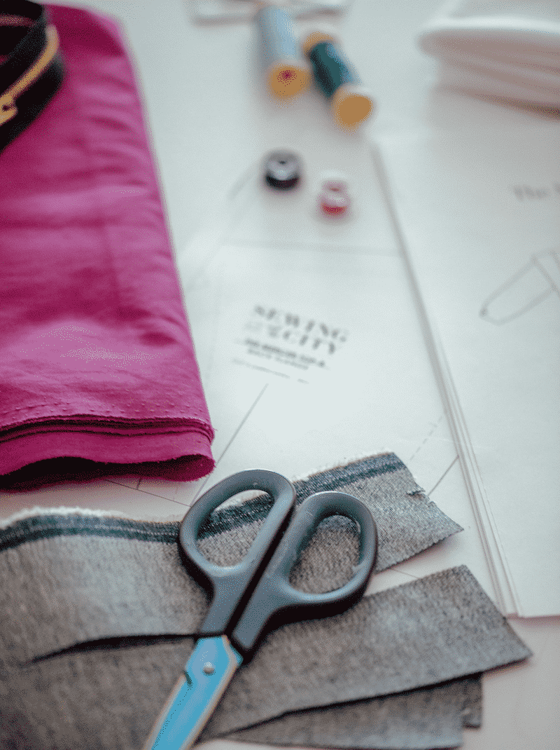 Flatlay of a Sewing and the City pattern with scissors and thread