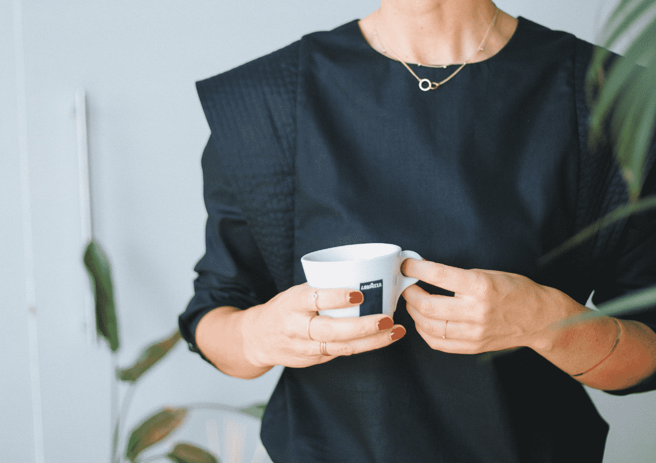 Christine wearing a black long sleeve Mercer holding a coffee cup